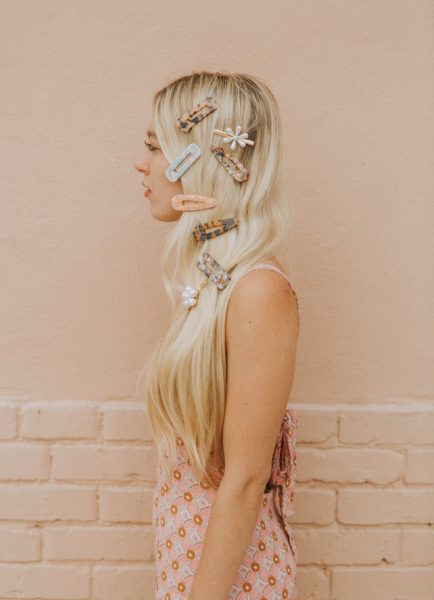 woman side long blonde hair multiple hair clips barrettes peach wall background the big hair clip trend for thin hair viviscal hair blog