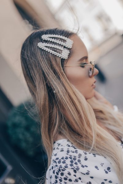 blonde young woman side two big pearl hair clips the big hair clip trend for thin hair viviscal hair blog