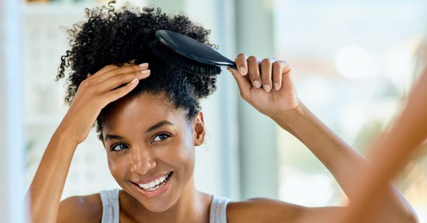 smiling african american woman mirror brushing curly hair how to use hair fiber powder viviscal hair blog