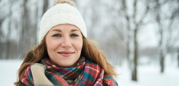 confident woman outside snow winter hat plaid scarf trees the seasonal hair shedding cycle viviscal hair blog