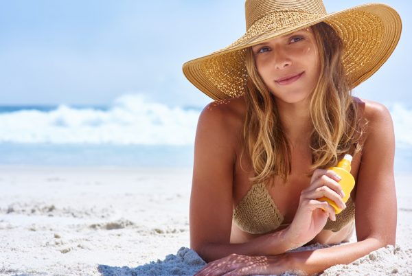 summer woman lying on beach sunshine hat the seasonal hair shedding cycle viviscal hair blog