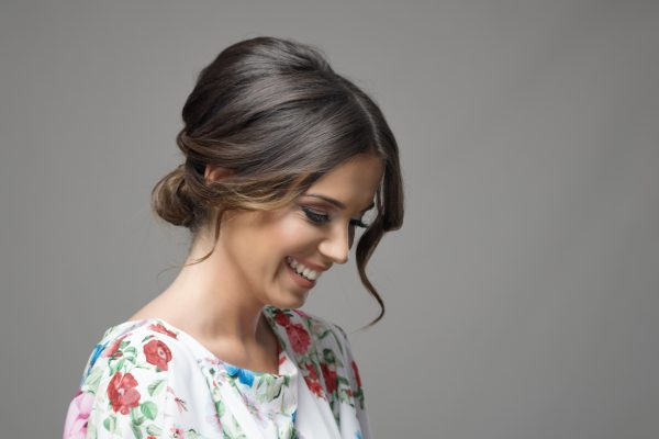 Brunette woman smiles shyly down, her hair is in a romantic chignon bun hairstyle for valentines day
