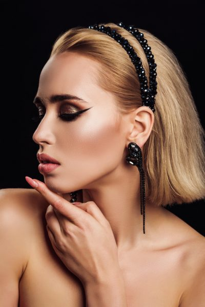 glamorous woman wears a black rhinestone headband in her blonde hair