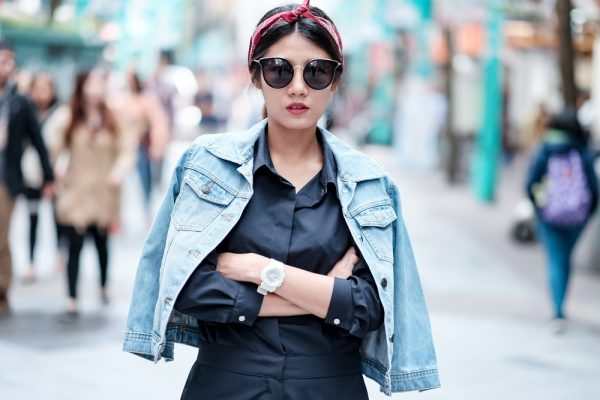 woman walks down the street, her hair in a scrunchie headband, sunglasses on her face
