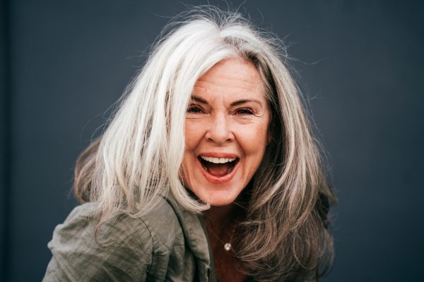 laughing woman gray mid length hair dark background what your hair says about you viviscal hair blog