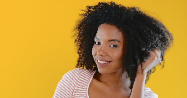 naturally curly woman african american holding hair yellow background wash and go hairstyle what your hair says about you viviscal hair blog