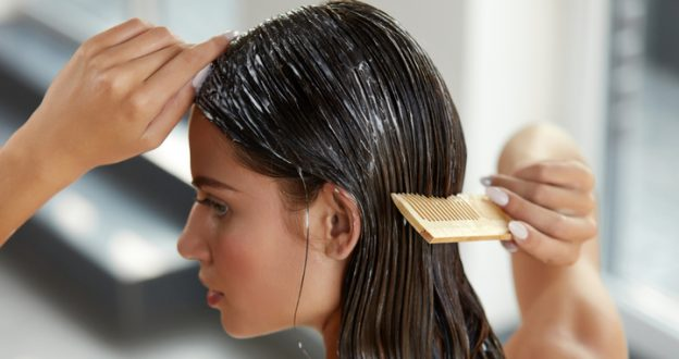 woman conditioning her wet hair with wide comb viviscal blog