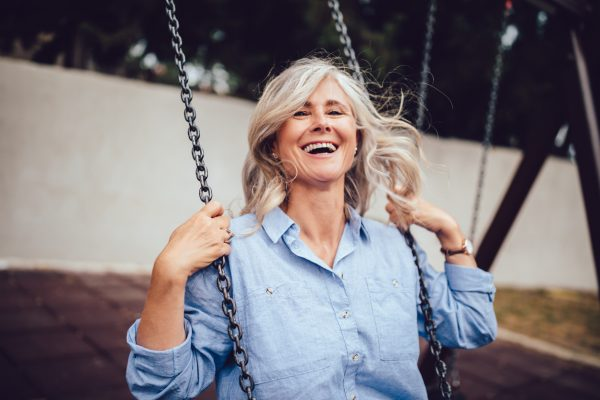 laughing woman swing gray hair blue shirt what your hair says about you viviscal hair blog